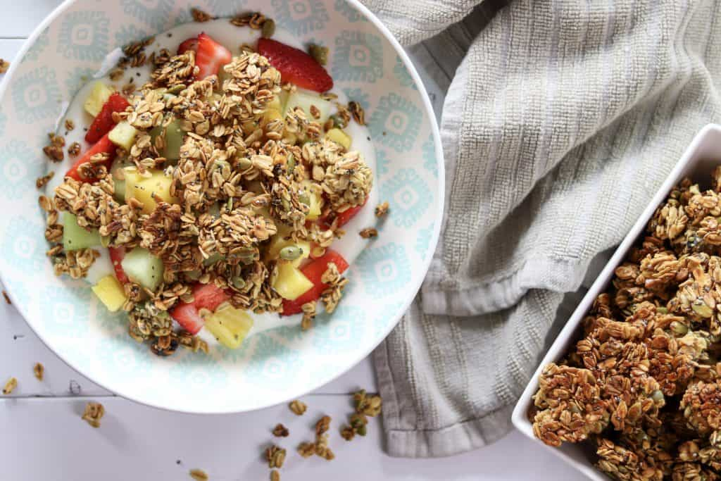 a bowl of yogurt, fruit, and topped with maple walnut and honey granola.