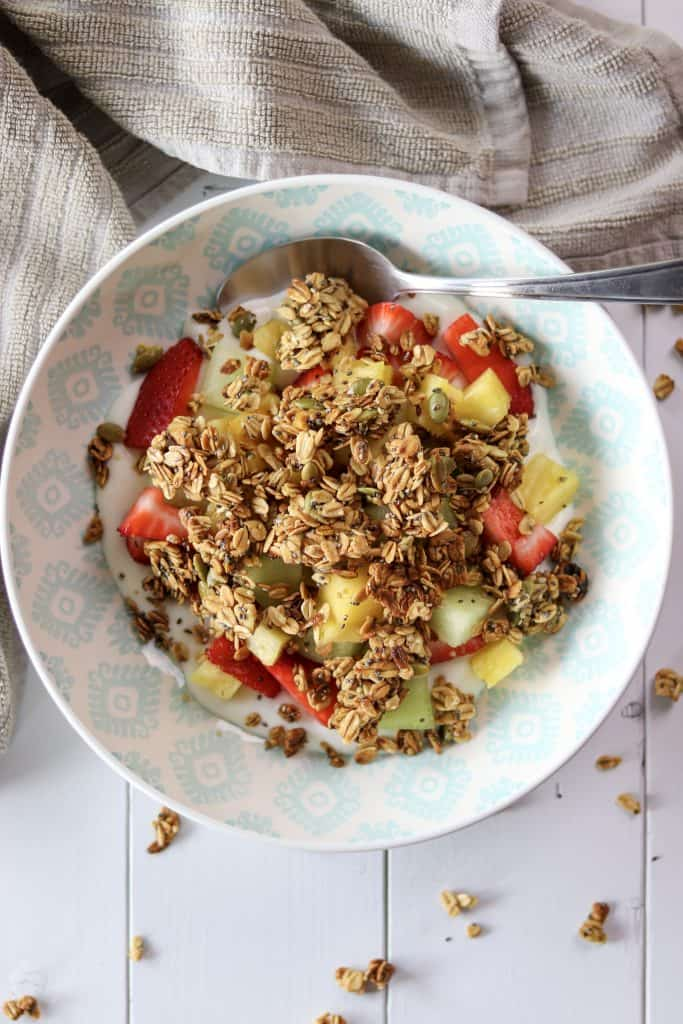 a bowl of yogurt, fruit, and topped with maple walnut and honey granola with a spoon on the edge