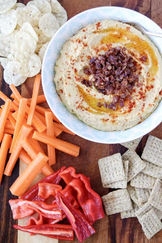 bowl of caramelized onion and roasted garlic hummus on a serving board with tortilla chips, crackers, carrots, and red peppers