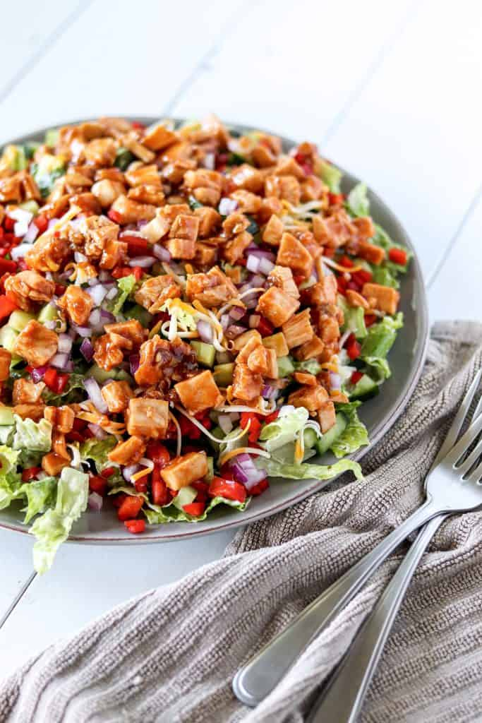 honey hot chicken salad on a large serving plate with two forks laying on a napkin