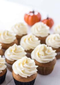 pumkin spice cupcakes with pumpkin in the background