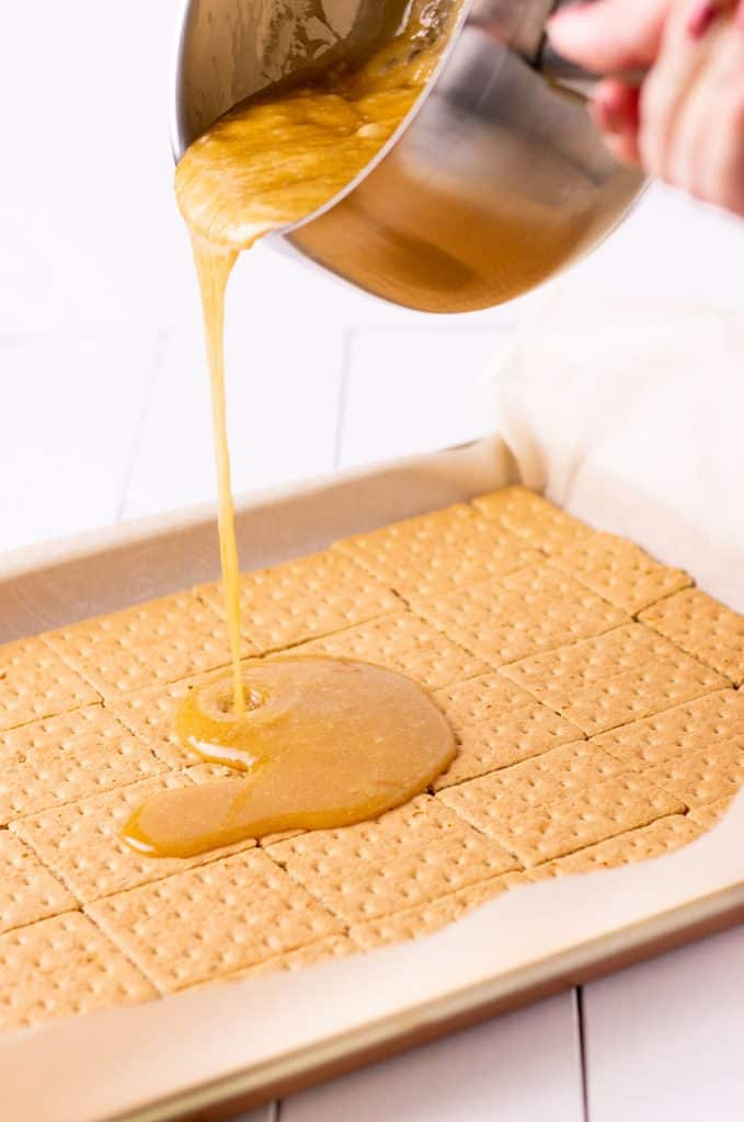 pouring the caramel over top of the graham crackers