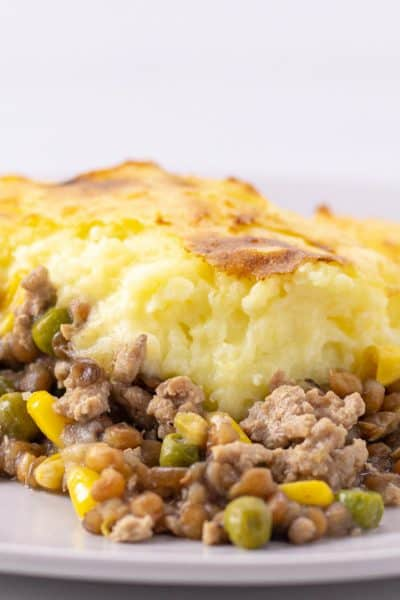 a serving of turkey shepards pie on a plate with a glass of red wine in the background