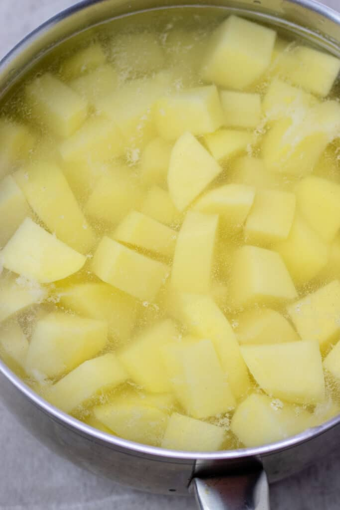 all of the potatoes in a saucepan filled with water, ready to be boiled