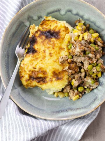 a serving of turkey shepards pie in a blue bowl with a fork and a gray napkin on the side