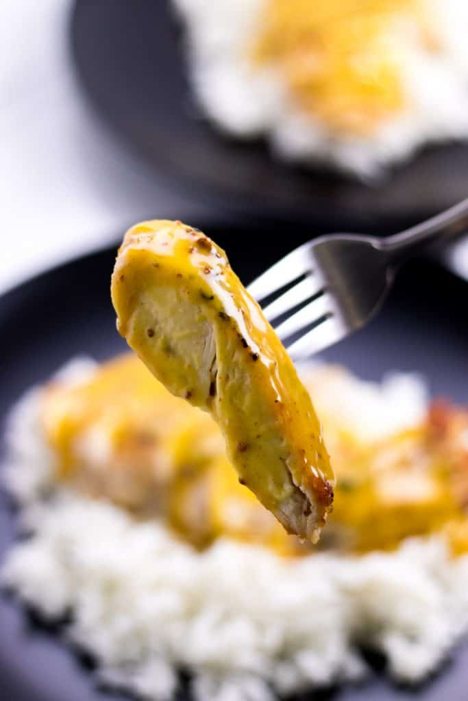 a piece of creamy honey mustard chicken on a fork ready to eat