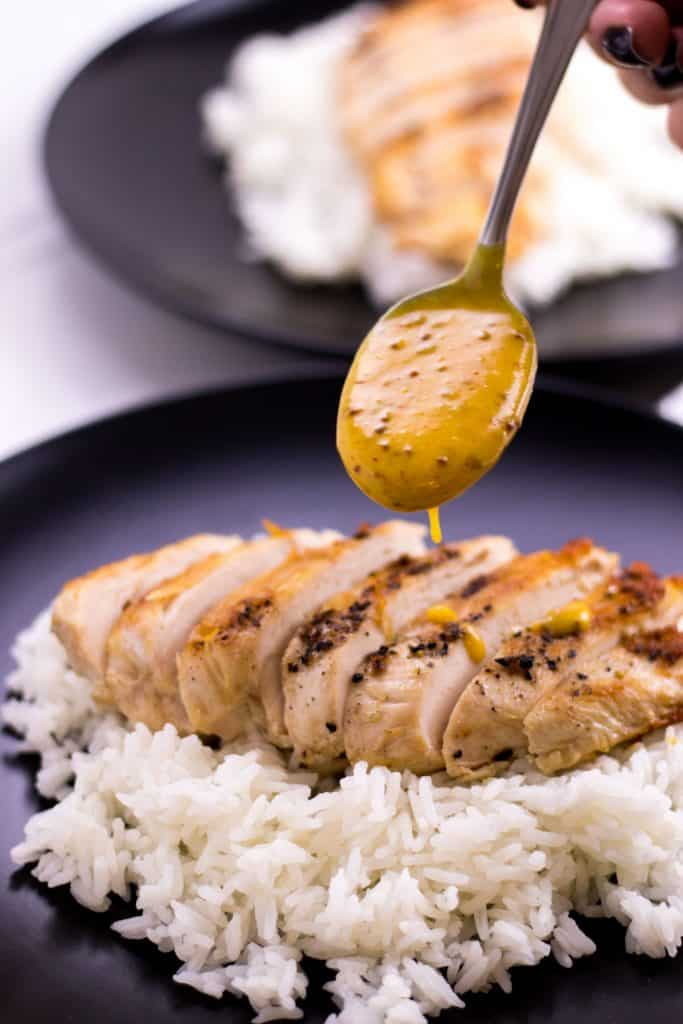 spooning the creamy honey mustard sauce onto the sliced chicken breast