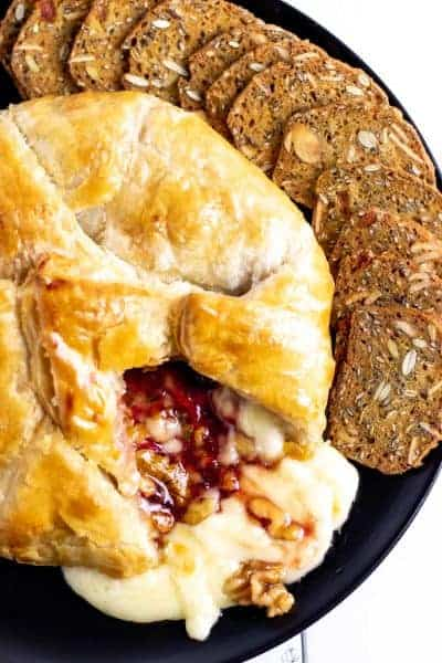 cutting into the spicy strawberry and walnut baked brie