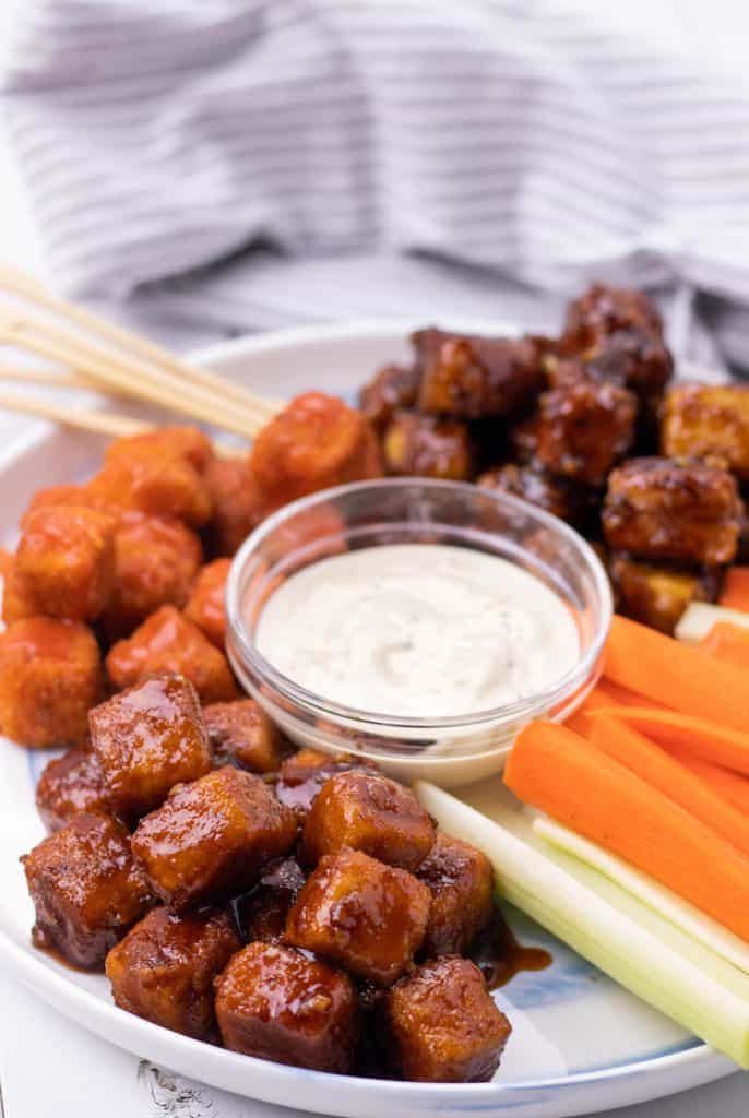 crispy tofu bites 3 ways served on a large platter with ranch dipping sauce and fresh veggies