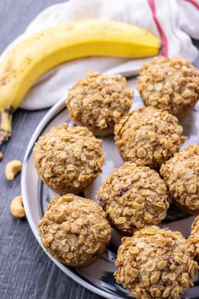 Banana Oat Blender Muffins on a serving dish with cashews sprinkled in the background and a ripe banana