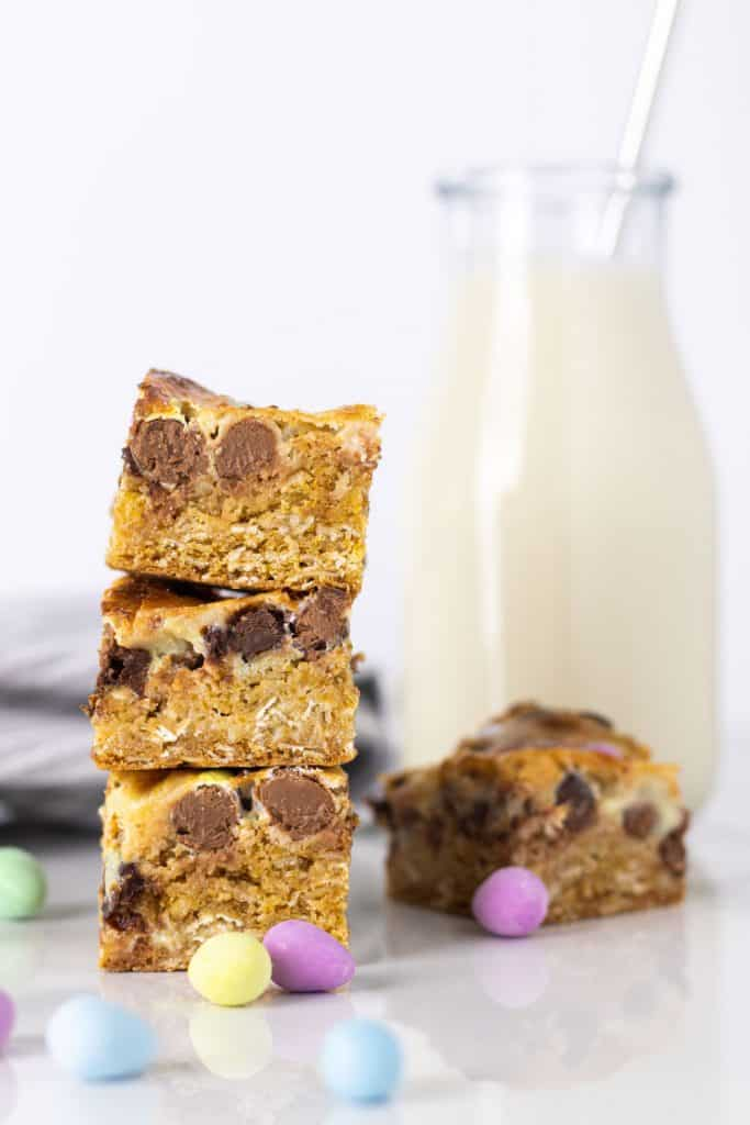 a stack of mini egg cookie bars with a jar of milk in the background