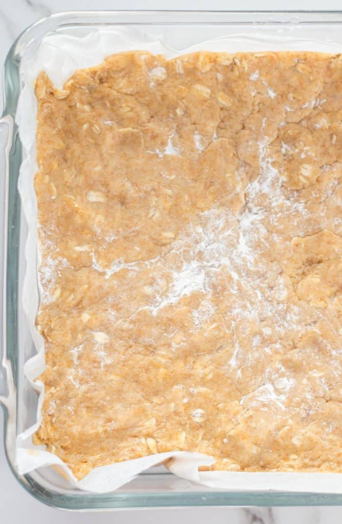 cookie bar batter pressed into the baking dish