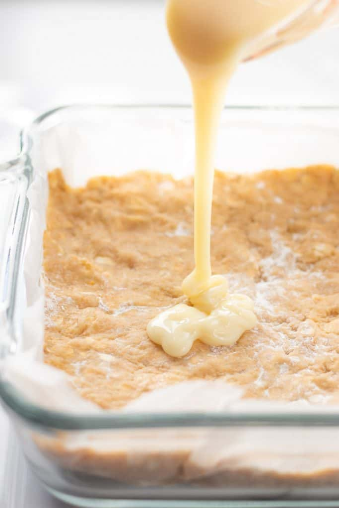 pouring the sweetened condensed milk on top of the cookie bar batter