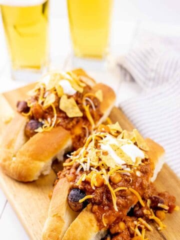 Fully loaded chili dogs, prepared and served on a wooden serving board