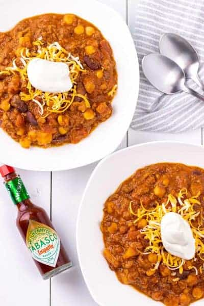 hawaiian chipotle chili served in white bowls topped with sour cream and shredded cheese