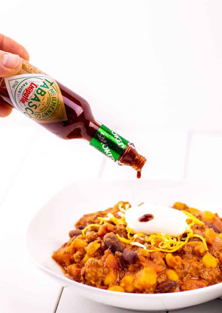 adding a little bit more chipotle Tabasco® Sauce on top of a bowl of chili
