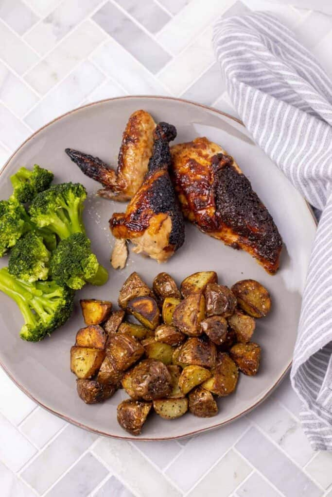 Bourbon Barbecue Roast Chicken pieces cut and served on a grey plate with pan fried hash browns and steamed broccoli