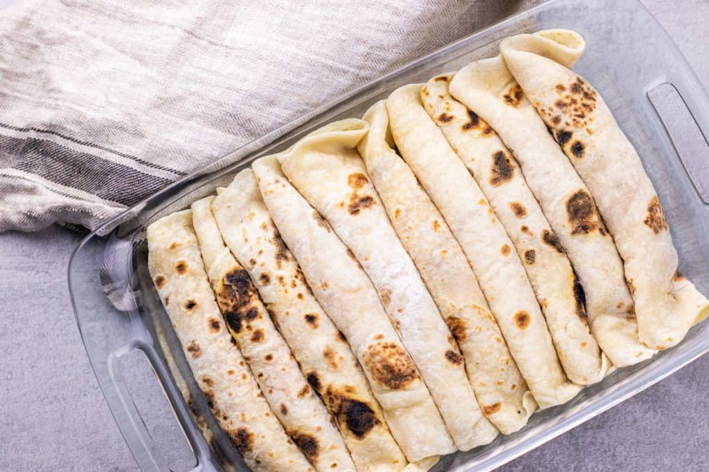 all of the breakfast enchiladas assembled, rolled up, and placed in a casserole dish.