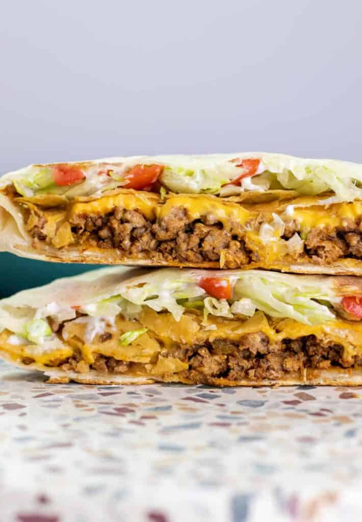 a cooked crunchwrap supreme cut in half and stacked to show the layers within