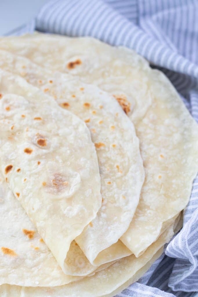 A plate of cooked flour tortillas being covered by a tea towel