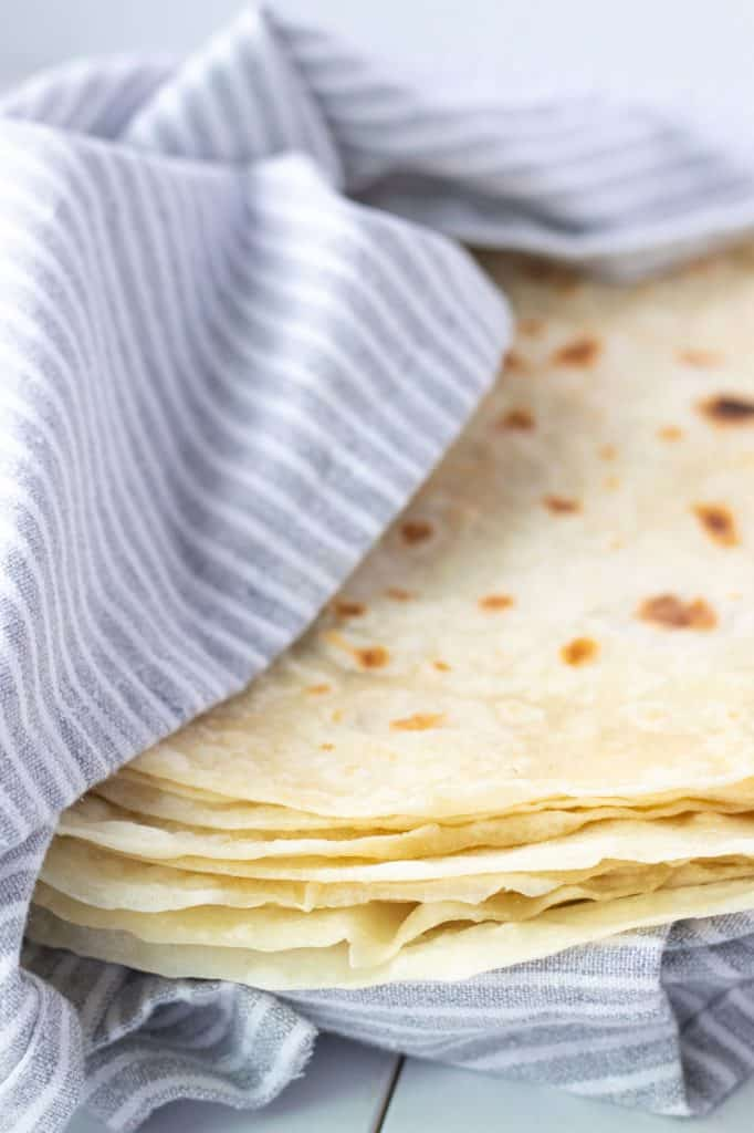 a stack of homemade flour tortillas on a plate, covered with a tea towel