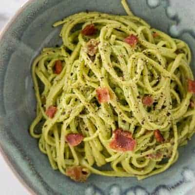 A serving of avocado carbonara in a blue bowl with some peppercorns in the background