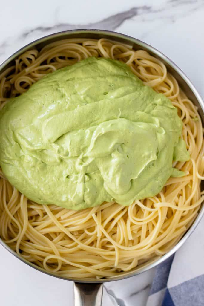 pouring the prepared avocado carbonara sauce overtop of the cooked linguini noodles