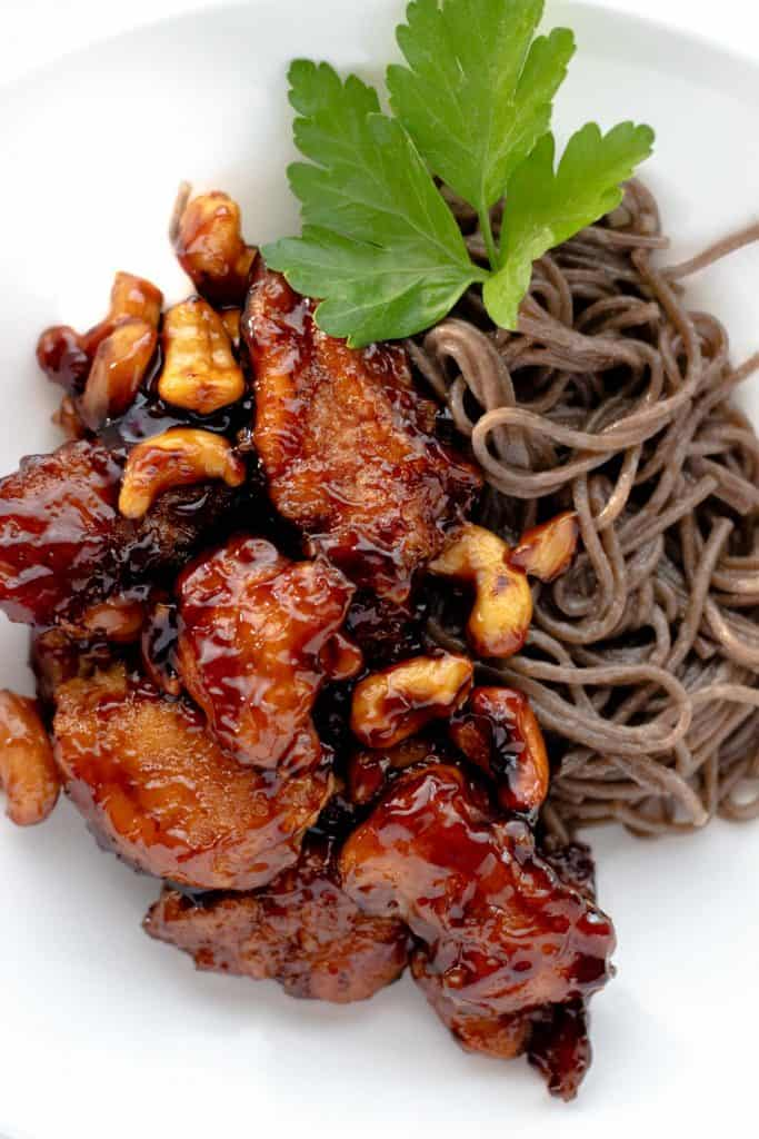cashew chicken served with buckwheat noodles and garnished with a piece of fresh parsley