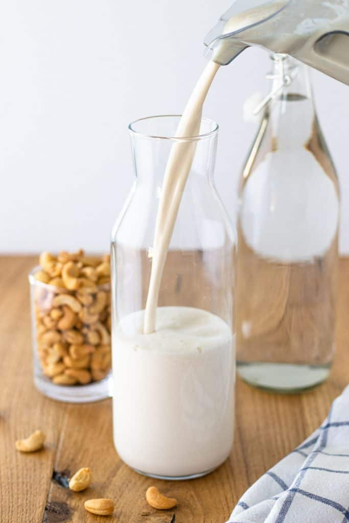 pouring the prepared cashew milk into a large jar for storage