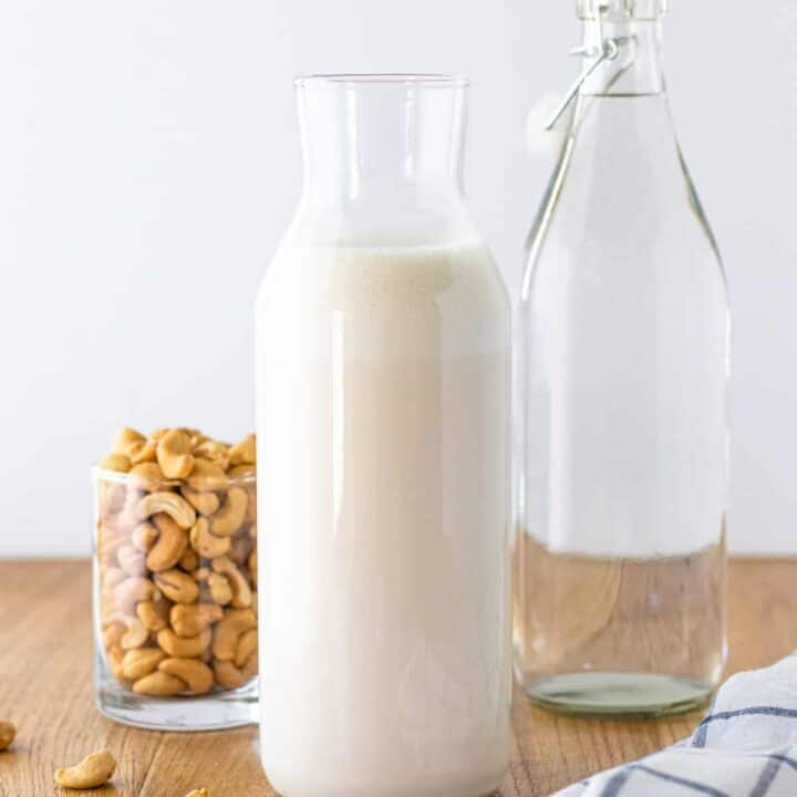 A prepared jar of cashew milk, with a carafe of filtered water and a bowl of raw cashews in the background