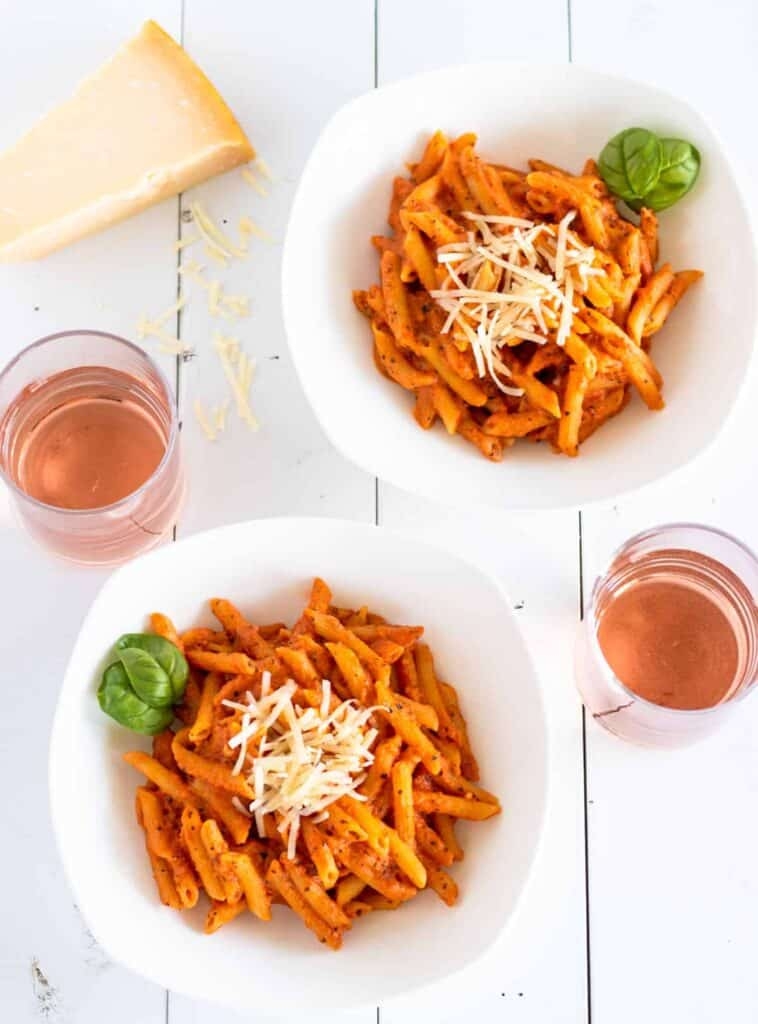 two bowls of rose penne served with grated parmesan cheese, fresh basil, and a glass of rose wine on the side