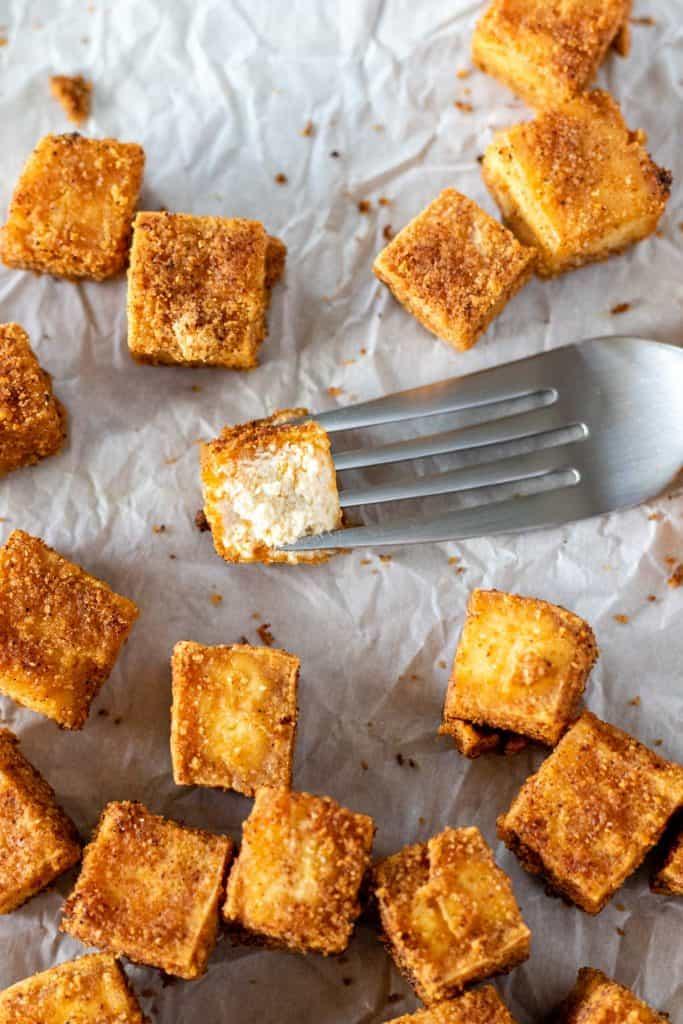 a piece of crispy baked tofu, bitten in half on a fork