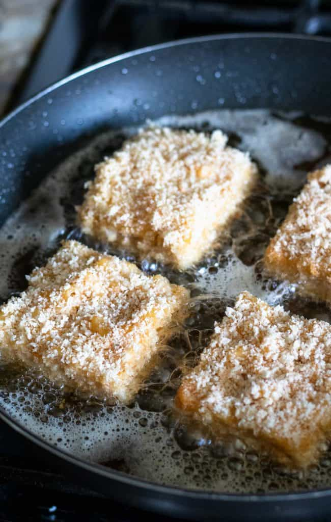 frying the breaded mac and cheese squares in vegetable oil until golden brown