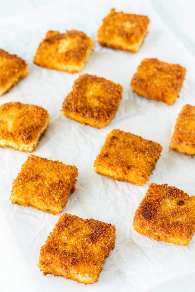 mac and cheese bites after they have been fried to a golden brown colour, laid out on a piece of parchment paper