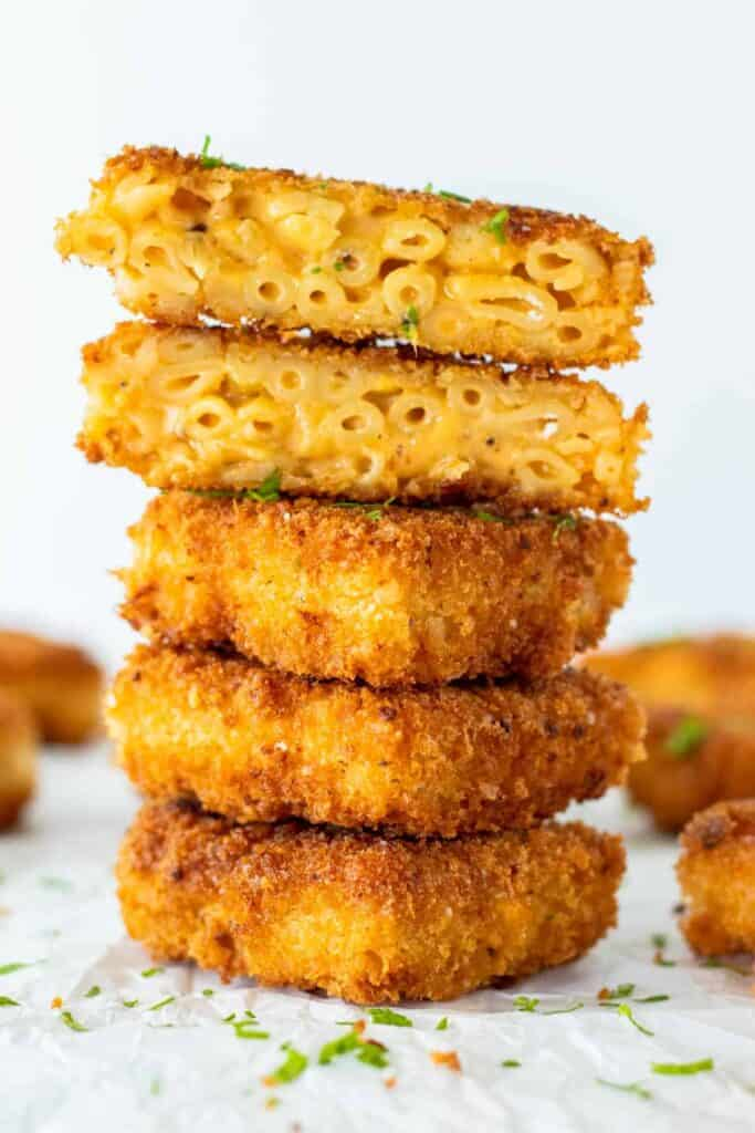 a stack of mac and cheese bites with the top two cut open to expose the cheesy insides