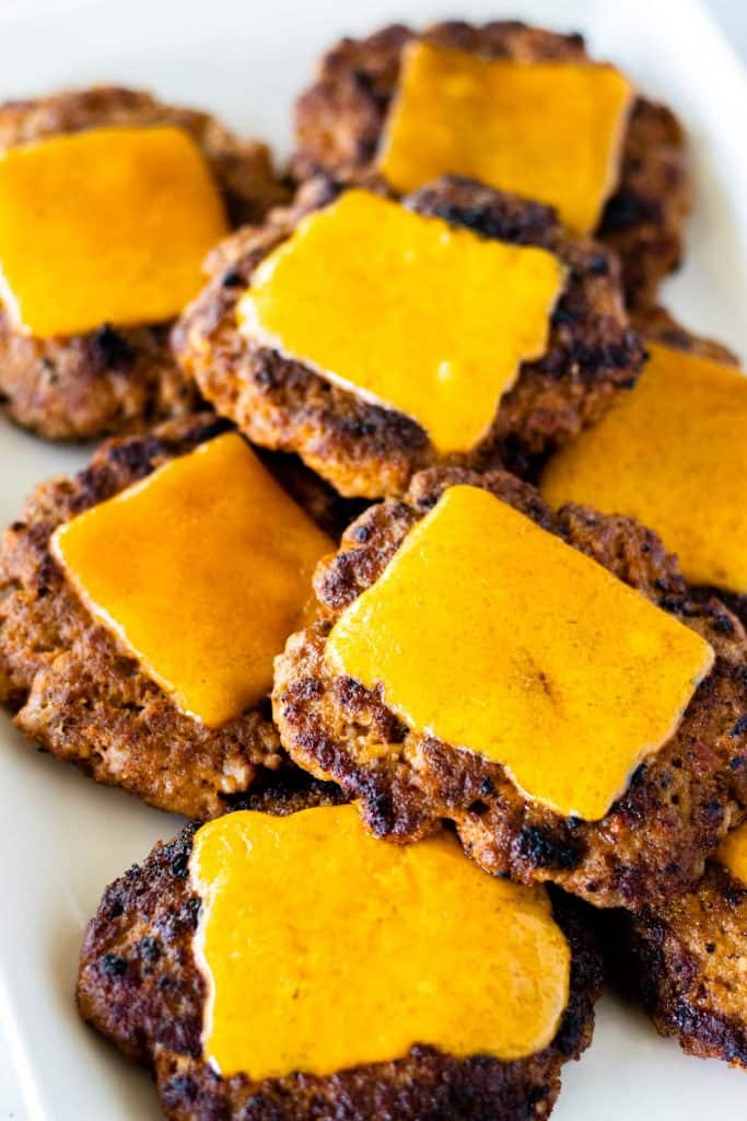 a prepared and cooked plate of chorizo slider patties topped with melted cheddar cheese