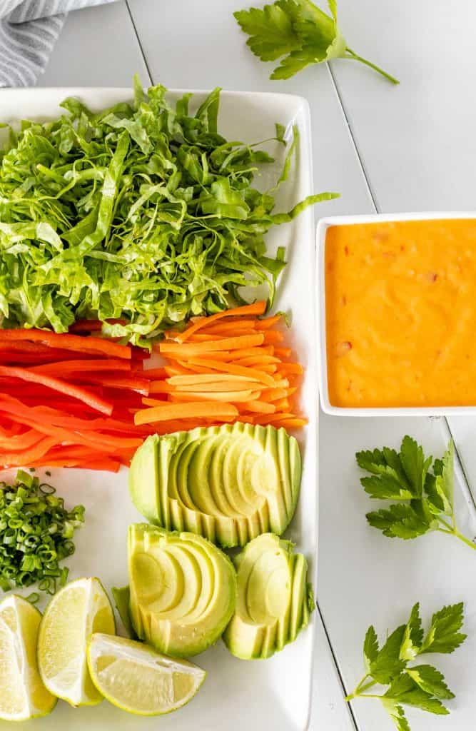 serving plate filled with shredded butter lettuce, bell peppers, carrots, avocado, scallions, lime wedges and a bowl of sweet chili sriracha mayo on the side