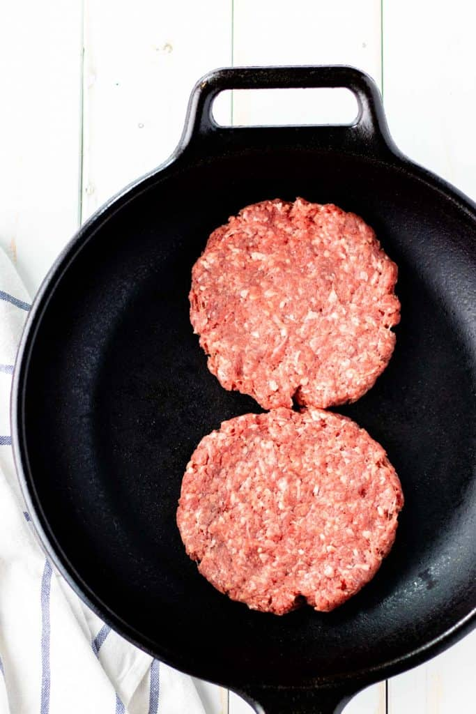 burger patties in a cast iron pan, ready to be cooked