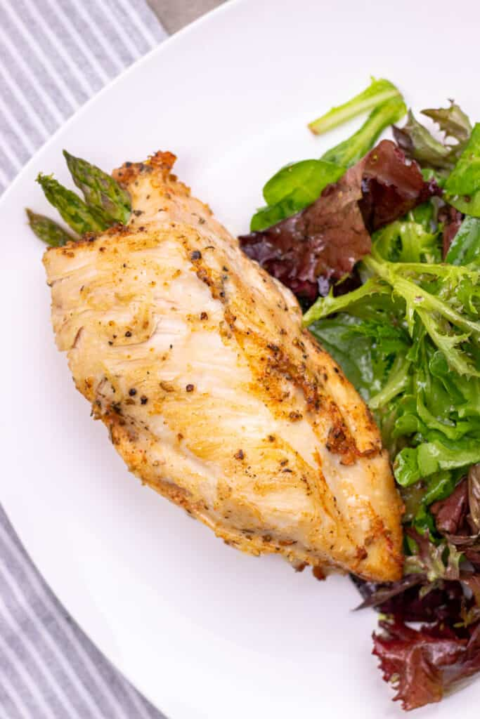 serving a asparagus and bacon stuffed chicken breast alongside a lite side salad