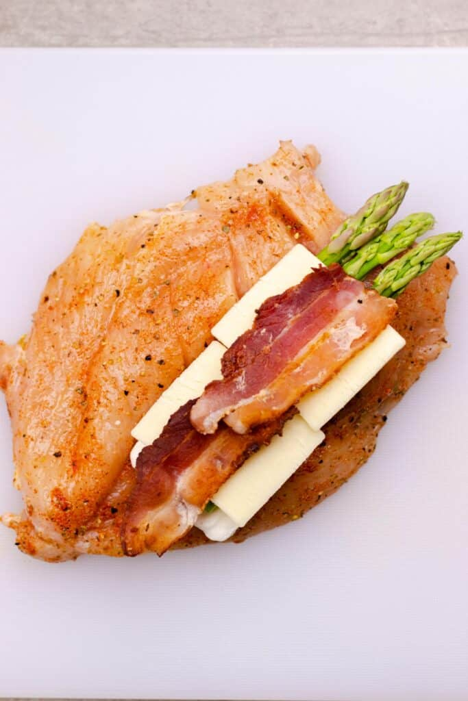 stuffing the spiced chicken breast with cream cheese, asparagus, mozzarella cheese, and bacon