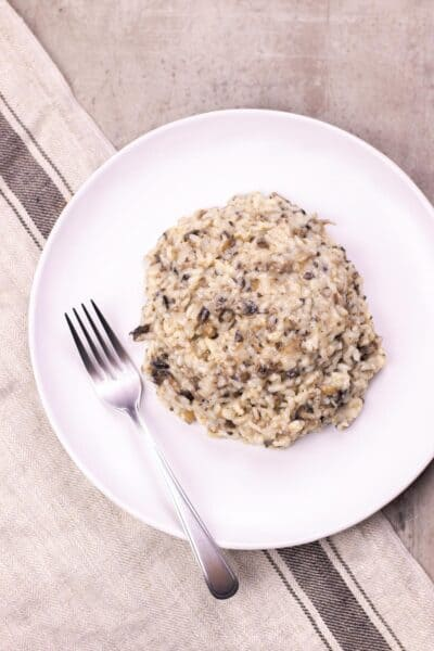 A serving of mushroom risotto on a white plate with a fork on the side