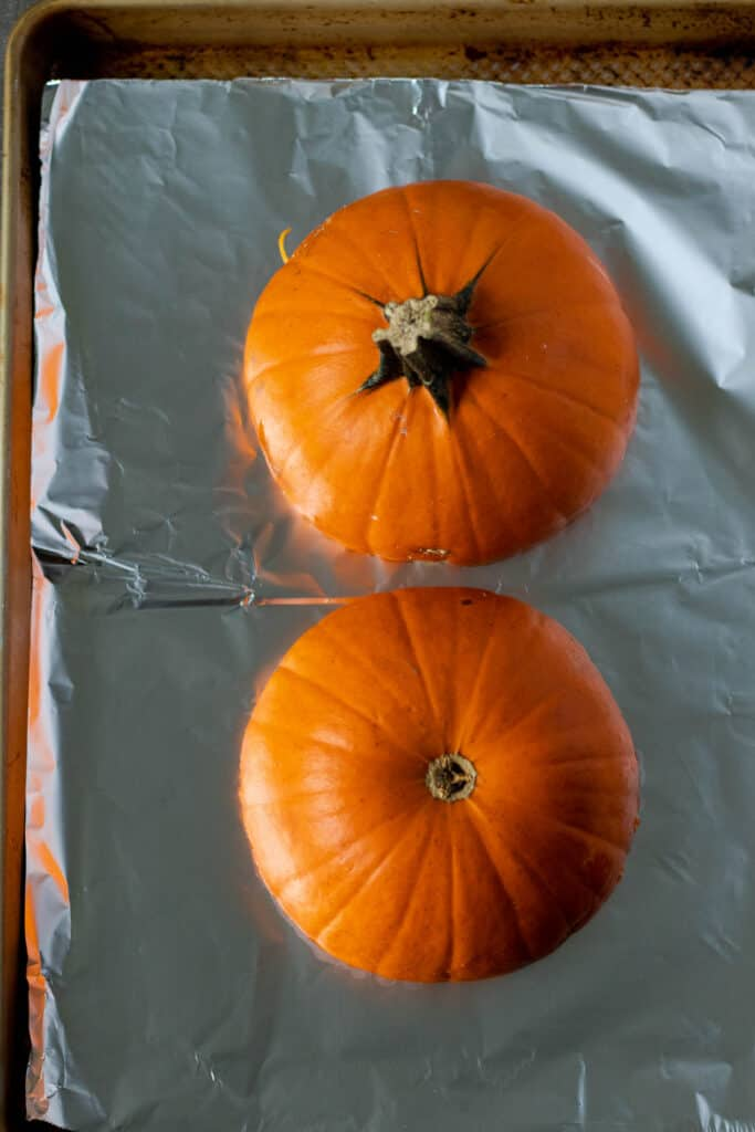 placing the prepared sugar pumpkin face down on aluminum foil to bake in the oven for about 45 minutes
