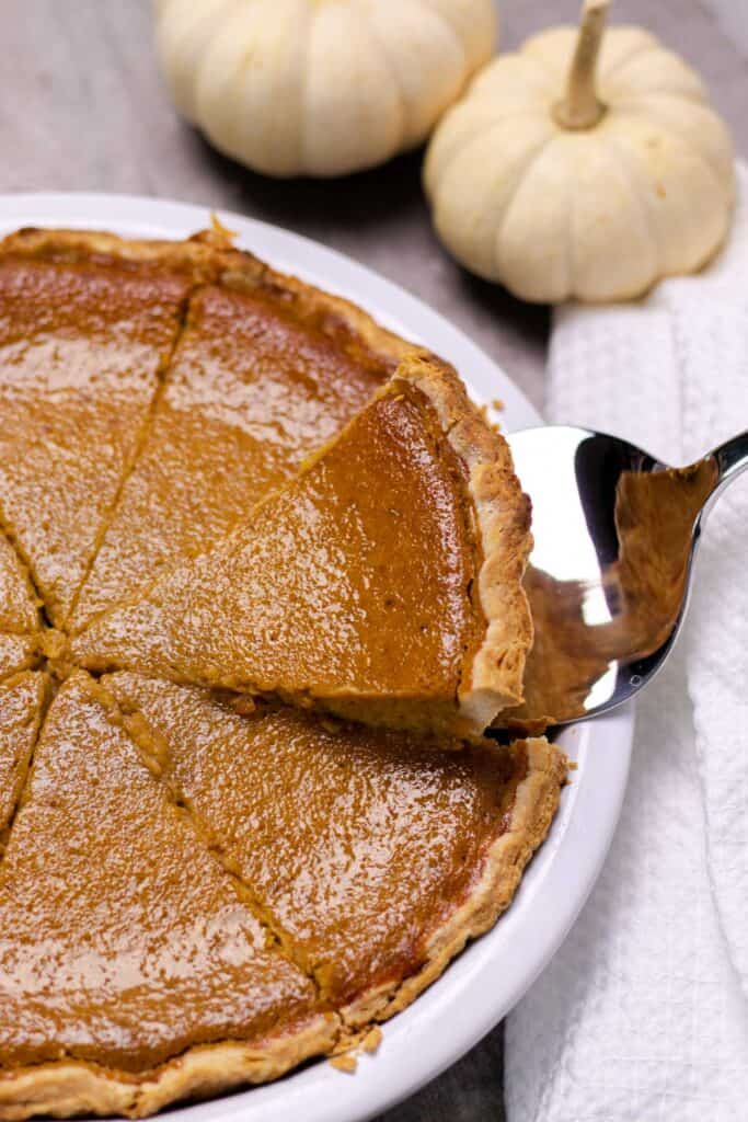 pulling a slice of the pumpkin pie out of the pie plate with a silver pie server