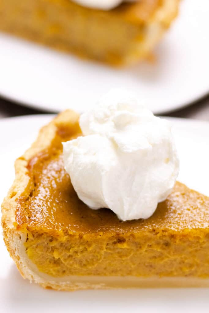 a piece of pumpkin pie on a white plate, topped with homemade whipped cream