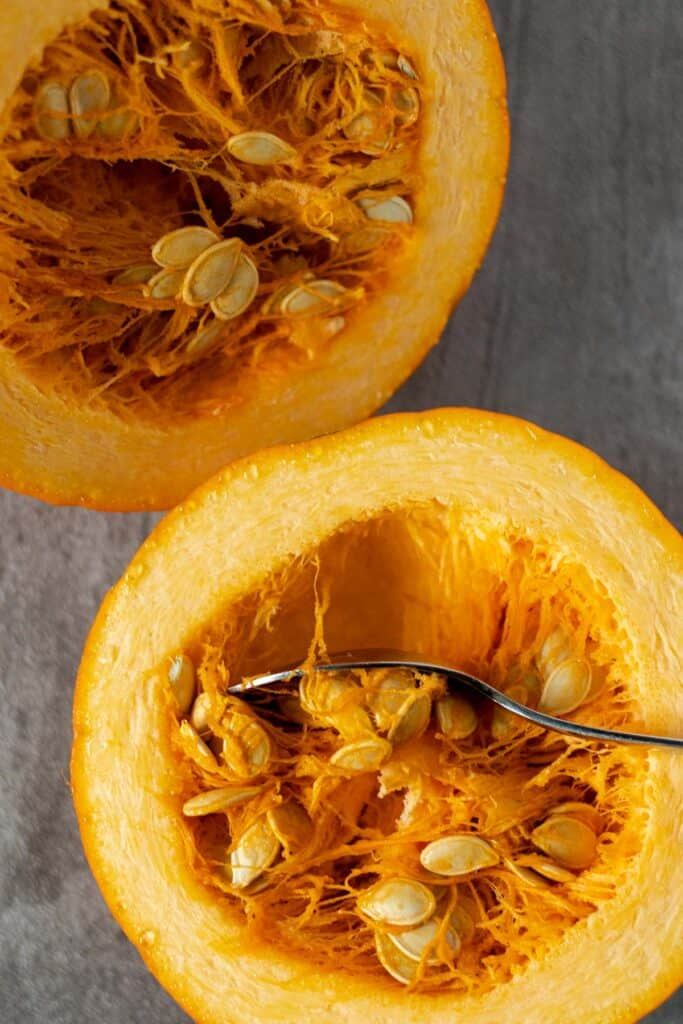cutting the sugar pumpkin in half and removing the seeds
