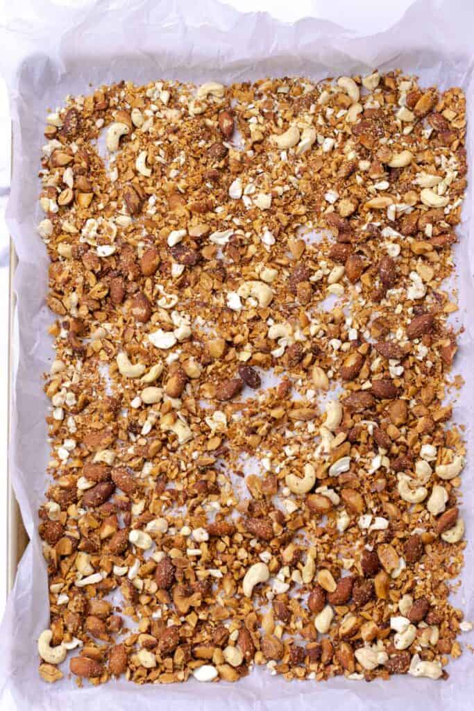 spreading out the roasted almonds and cashews on a baking sheet lined with parchment paper