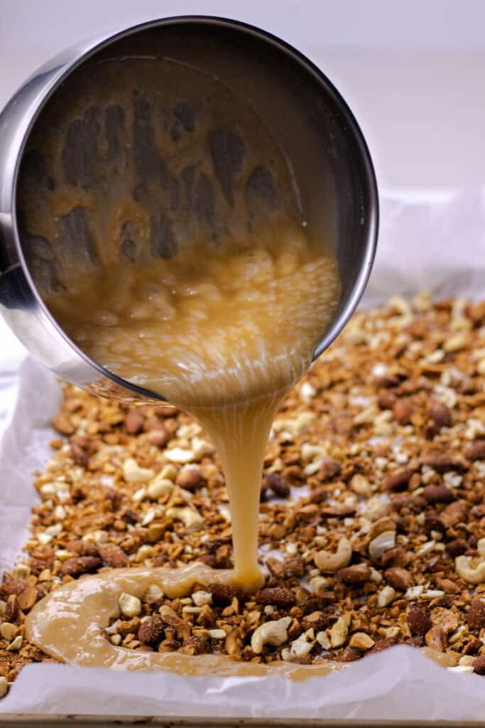 pouring the prepared toffee on top of the nuts
