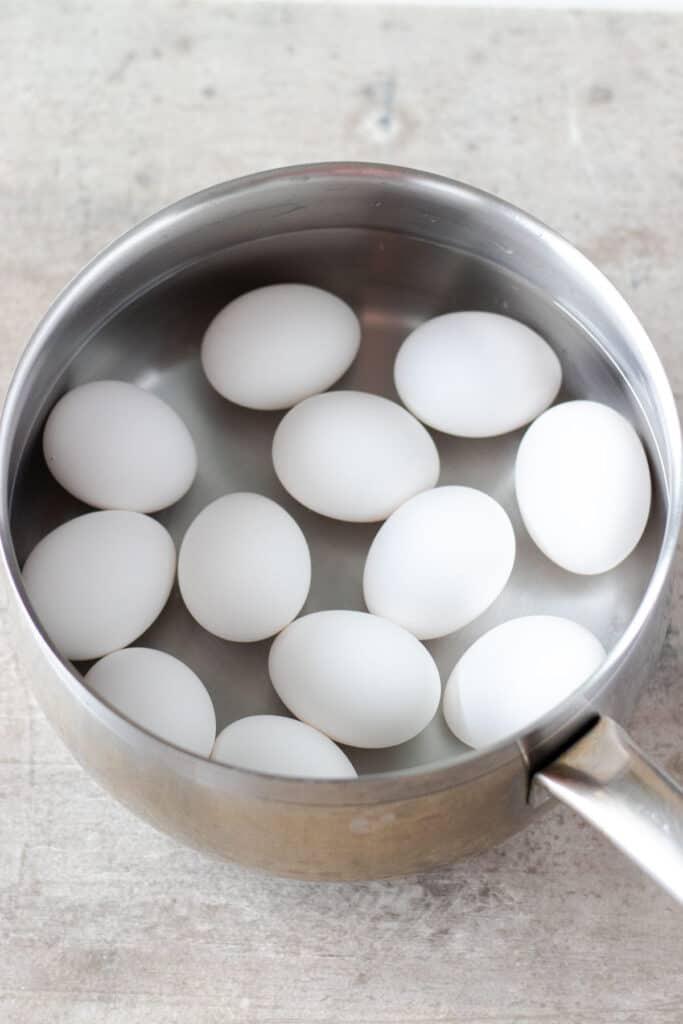 putting the eggs into a saucepan and covering them with cold water to cook