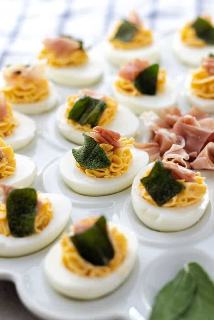 a close up showing one devilled egg, filled with the butternut squash mixture and topped with a piece of prosciutto and a crispy butter fried sage leaf