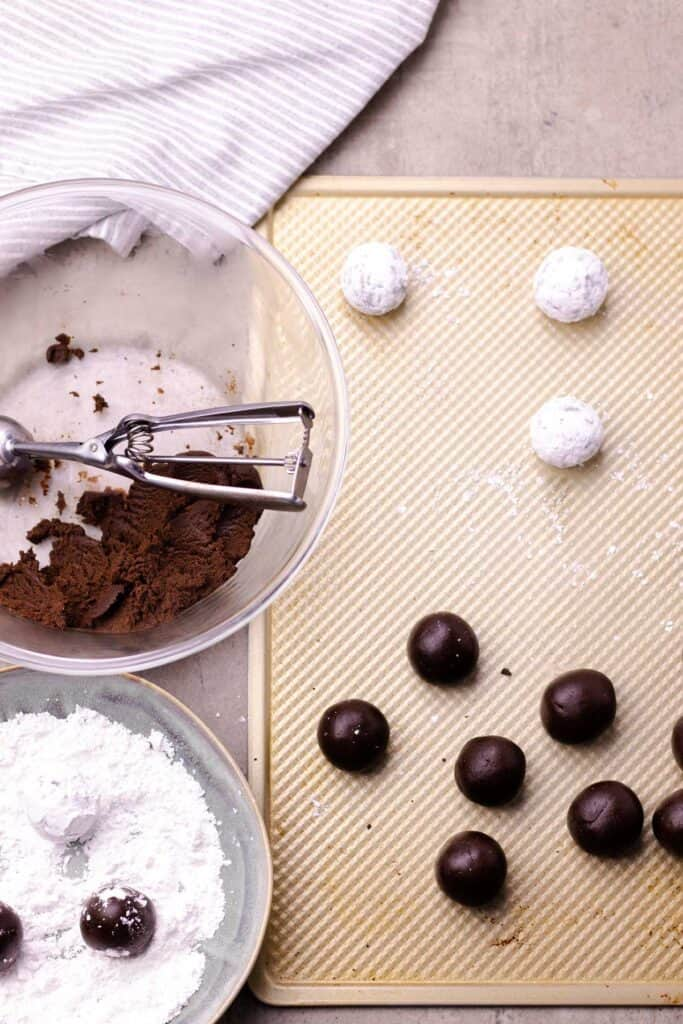 rolling the cookie batter into balls, dipping them in icing sugar, and placing them on a baking sheet